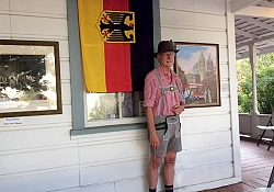 "Gene Stirm was dressed in German Lederhosen, refecting his German heritage for the July ""Art on the Porch"" event. Here he appears next to the German Flag."