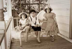 Three barefoot children in vintage clothing pose on a wicker chaise on the Errea House porch, under the rose arbor.