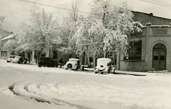 Christmas day in 1936, the height of the Great Depression, shows a deep covering of snow on Green Street. The Bank of Tehachapi is on the right (now the location of The Tec Computer Store). Following from right to left are Weferling's Dress and Dry Goods Store, the Summit Hotel and the Clark Hotel on the corner of F Street and Green Street.