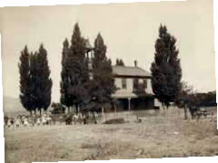 The two-story Summit School in 1904 with trees and a picket fence. There is a hitched up horse and buggy at right with women, children and a man holding hands at left.