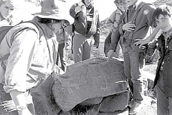 Photo of group standing around a petroglyph at Nettle Springs (now Tomo Kahni State Park) April of 1988.